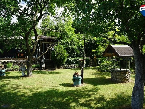 Sonniger Freizeitgarten mit urigem Natursteinhaus